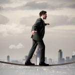 Businessman is balancing on a rope sky clouds high up suit scary city