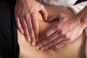 osteopathy procedure on the belly, forming a heart with the hands massage