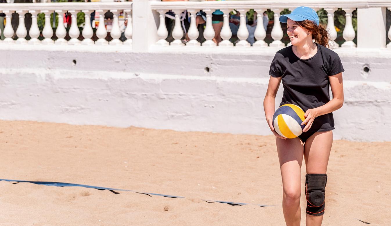 Young caucasian woman in bikini playing beach volleyball